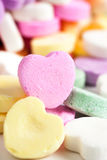 Candy Hearts. Pastel colored candy hearts in a pile on a white surface Stock Photos