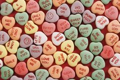 Candy hearts on red. Large group of colorful candy hearts with sayings on them arranged on red background stock photo