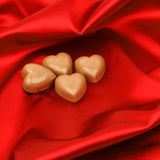 Candy hearts on red satin Stock Images