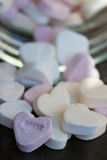 Candy Hearts with sorry. Colourful Candy hearts on a black plate stock image