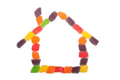 Candy house. Pieces of candy forming the shape of a house isolated on white background stock photography