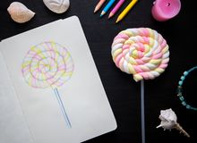 Candy illustration and candy on stick. Artist workplace with sketch book top view photo. Marshmallow candy on table. Food sketch of dessert. Sweet candy for Royalty Free Stock Image