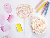 Candy illustration and candy on stick. Artist workplace with watercolor illustration. Watercolor study top view photo. Marshmallow candy on table. Food sketch Royalty Free Stock Image
