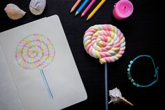 Candy illustration and sweet candy on stick. Artist workplace with sketchbook top view photo. Marshmallow candy on table. Food sketch of dessert. Sweet candy Royalty Free Stock Images