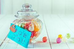 Candy jar filled with candies with a blue tag. Close-up view of an antique candy jar filled with colorful candies with a blue tag with a romantic, For You Royalty Free Stock Photos