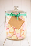 Candy jar filled with marshmallows and a blank tag Royalty Free Stock Image