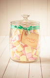 Candy jar filled with marshmallows and a tag Royalty Free Stock Photo