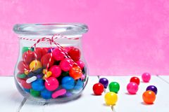 Candy jar of gum balls on pink background. Candy jar of colorful gum balls on white wood against a pink background royalty free stock images
