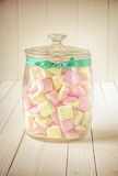 Candy jar with marshmallows and green ribbon Royalty Free Stock Photo