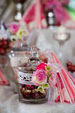 Candy jar. With pink, red and white flowers on a table stock images