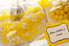 Candy jars. Jars full of yellow and white candies with sign telling the candy flavors. They are offered to guests during a wedding celebration Royalty Free Stock Image