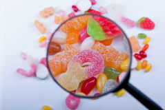 Candy and jelly. Coloured candy and jelly seen through magnifying glass Royalty Free Stock Photography