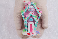 Candy land Christmas. Female hands in white knitted cozy mittens holding colorful candy house christmas tree decoration on a white Royalty Free Stock Photo