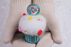 Candy land Christmas. Female hands in white knitted cozy mittens holding colorful cupcake christmas tree decoration on a white sno Stock Images