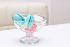 Candy macaroons lies in a glass vase for sweets on a white table Royalty Free Stock Images