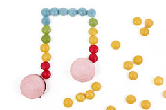 Candy musical note. Multicolored macaron chocolate candy musical note on white background Stock Photos