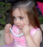 Candy Necklace. A little girl dressed in a princess dress for a birthday party eating a candy necklace.  She looks as if she's enjoying it very much Stock Photo