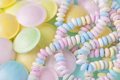 Candy necklace. On a blue pastel colored background royalty free stock image