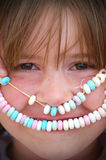 Close up of little girl big brown eyes with a happy face candy necklace for a mouth. Royalty Free Stock Photo