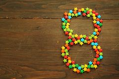 Candy number eight. Number eight made with star shape candies on a wooden table Royalty Free Stock Photo