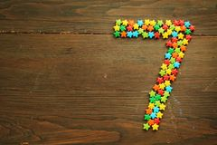 Candy number seven. Number seven made with star shape candies on a wooden table Stock Photography