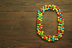 Candy number zero. Number zero made with star shape candies on a wooden table stock image