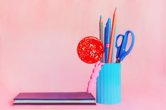 Candy with pink and blue stationery set and notepad. Blue pencil-box with pencils, scissors and red round candy beside notepad on a  pink background. Selective Royalty Free Stock Photo