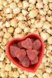 Candy and popcorn. Heart shape candy bowl on sweet pop corn for Valentine Day royalty free stock image