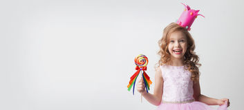 Candy princess with lollipop. Small princess girl in crown holds a large spiral decorated lollipop candy royalty free stock photography