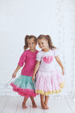 Candy princess. Studio portrait of two cute little princess girls wearing holiday candy tutu skirt holding magic wand Royalty Free Stock Image