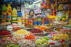 Candy Seller, Ho Chi Minh City, Vietnam. Woman candy vendor talks on the cell phone in the Binh Tay Market, Cholons (Chinatowns) biggest market, in Ho Chi Minh Stock Photo