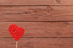 Candy in the shape of a heart. Valentine`s day Lollipop on wooden background. Valentine`s day background, wedding day. Candy. Concept of love stock images