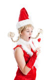 Candy shock. Cute young girl in santa outfit looking shocked at her lollipop Royalty Free Stock Photo