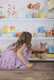 Candy shop. A girl putting candies on the shelf Stock Images