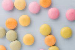 Candy. Small round candy-colored pastels on pastel background royalty free stock images