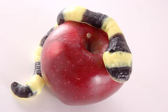 Candy snake on apple. Candy yellow snake on red apple, original sin concept Royalty Free Stock Photo