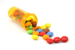Candy spilling out of pill bottle Royalty Free Stock Photography