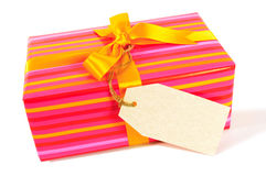 Candy stripe Christmas or birthday present, yellow gold ribbon, blank gift tag or label isolated on white background Royalty Free Stock Photography