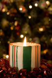 Candy Striped Candle. Selective focue on candy striped candle in front of the Christmas Tree with soft focus Stock Photos