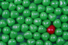 Candy sweets background. Single red candy sweet in background of green ones stock image