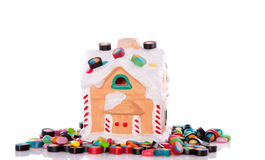 Candy sweets on a small house. A little colorful candy house with cheerful assorted candy sweets isolated on white background royalty free stock image