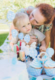 Candy-table. Baby boy eat birthday cake with hands. His mother take him. Birthday party in park on picnic. Stock Photography