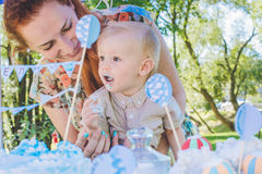 Candy-table. Baby boy eat birthday cake with hands. His mother take him. Birthday party in park on picnic. Stock Photo