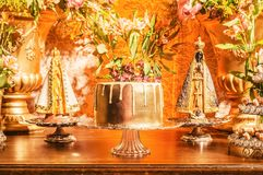 Candy table with a golden cake and some sweets around the cake o. F a wedding party. Flowers decoration and two Nossa Senhora Aparecida saints beside the cake Royalty Free Stock Image