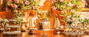 Candy table with a golden cake and some sweets around the cake o. F a wedding party. Flowers decoration and two Nossa Senhora Aparecida saints beside the cake Royalty Free Stock Photography