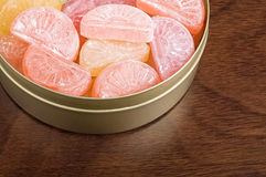 Candy in a tin. Fruit candies in tin on wooden table closeup Royalty Free Stock Image