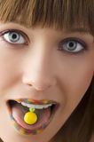 The candy on tongue. Close up of young girl with multicolor lips and a yellow candy on her tongue Royalty Free Stock Photos