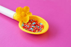 Candy in toy spoon Stock Image
