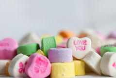 Candy Valentine Conversation Hearts Love. A macro shot of Valentine's Day candy conversation hearts saying love you royalty free stock photos