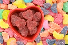 Candy. Valentine candy in heart shape bowl on colorful candy background royalty free stock image